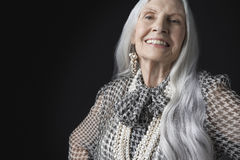 Senior Woman With Long Gray Hair Smiling. Portrait of a smiling senior woman with long gray hair against black background Royalty Free Stock Photography