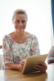 Senior woman looking at the camera using a digital tablet Stock Images