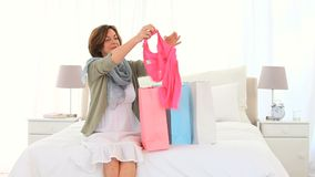 Senior woman looking at the clothes she has just bought stock footage