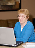 Senior woman looking at computer. Senior woman looking at a laptop with a pleased expression Royalty Free Stock Images