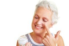 Senior woman looking at creme jar Royalty Free Stock Image