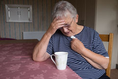 Senior woman looking depressed or worried with mental health issues. Senior grey haired woman sitting at table looking worried Stock Photography