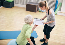 Senior woman looking at exercise plan with personal trainer. Senior women in a gym sitting on exercise ball and talking to her private trainer about exercise Royalty Free Stock Image