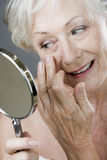 A senior woman looking at her face in the mirror Stock Images