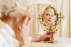 Senior woman looking at her face with sadness Stock Photos