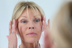 Senior woman looking at her skin in the mirror royalty free stock images