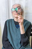 Senior woman looking through magnifying glass Royalty Free Stock Images