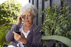 Senior woman looking at mobile phone Royalty Free Stock Photos
