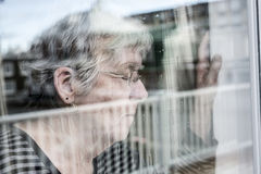 Senior woman looking out through a window like depress. A Senior woman looking out through a window like depress Royalty Free Stock Photos