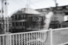 Senior woman looking out through a window like depress. A Senior woman looking out through a window like depress Stock Photos