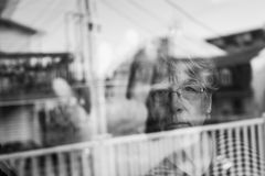 Senior woman looking out through a window like depress Stock Images