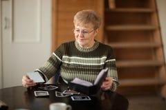 Senior woman looking photo. Senior woman viewing photo album in livingroom Royalty Free Stock Photography