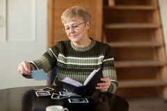 Senior woman looking photo. Senior woman viewing photo album in livingroom Royalty Free Stock Image
