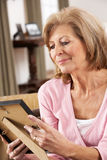 Senior Woman Looking At Photograph In Frame Stock Photo