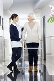 Senior Woman Looking At Physiotherapist While Using Walker Royalty Free Stock Photo