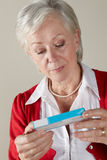 Senior woman looking at prescription drug pack Stock Image