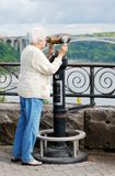 Senior woman looking at the rainbow bridge. Lone senior woman looking at the rainbow bridge from Niagara falls Ontario stock image