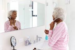 Senior Woman Looking At Reflection In Bathroom Mirror Brushing Hair royalty free stock photos