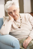 Senior Woman Looking Sad At Home. Senior Woman Looking Sad In Chair At Home royalty free stock photography
