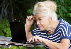 Senior woman looking at screen of laptop Royalty Free Stock Images