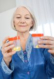 Senior Woman Looking At Tablet Bottles Stock Images