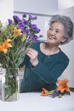 Senior Woman Looking and Touching a Bouquet of Flowers in the Kitchen Royalty Free Stock Images