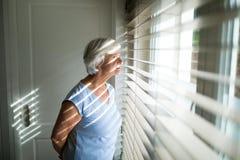 Senior woman looking through window in bedroom Royalty Free Stock Photos