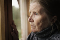 Senior woman looking in a window stock photography