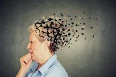 Senior woman losing parts of head feeling confused as symbol of decreased mind function. stock image