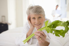 Senior woman lying on bed holding celery stick, smiling, portrait, close-up Stock Image
