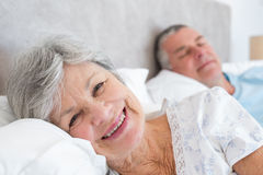 Senior woman lying on bed with man Royalty Free Stock Images