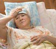 Senior woman lying at bed Royalty Free Stock Photos