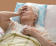 Senior woman lying at bed Royalty Free Stock Image