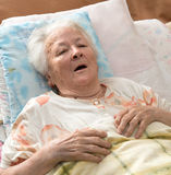 Senior woman lying at bed Royalty Free Stock Images