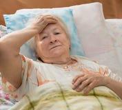 Senior woman lying at bed stock photo