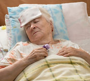 Senior woman lying at bed Stock Image