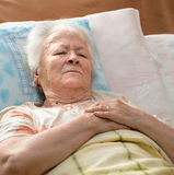 Senior woman lying at bed Stock Images