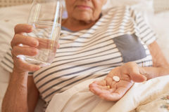 Senior woman lying in bed taking medicine in the morning Royalty Free Stock Photo