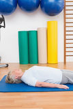 Senior woman lying on exercise mat Stock Photography