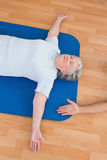 Senior woman lying on exercise mat Royalty Free Stock Image