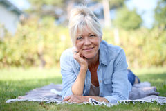 Senior woman lying in grass Stock Image