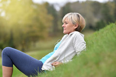 Senior woman lying in grass relaxing after jogging Stock Image