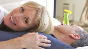 Senior woman lying on husbands  Royalty Free Stock Photos