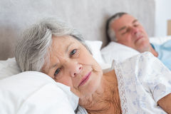 Senior woman lying with man in background Royalty Free Stock Images