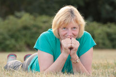 Senior woman lying outside and smiling behind hands Royalty Free Stock Photography