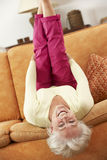 Senior Woman Lying Upside Down On Sofa At Home Royalty Free Stock Photography