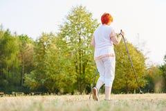 Senior woman makes a nordic walk Royalty Free Stock Photography