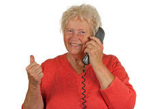 Senior woman makes OK gesture on telephone Royalty Free Stock Photography