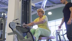 Senior woman makes pull up exercise on training apparatus in the gym. Trainer controls the process of training the elderly woman. Senior woman has a healthy stock video