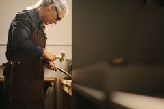 Senior woman making jewelry royalty free stock photography